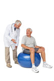 Male therapist looking at senior man sit on exercise ball. Male therapist looking at senior men sit on exercise ball over white background Royalty Free Stock Photos