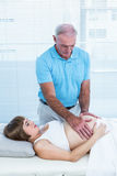 Male therapist massaging belly of pregnant woman. Male therapist massaging belly of pregnant women at health center Royalty Free Stock Images