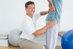 Male therapist massaging mans lower back at gym hospital Stock Photography