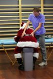 Male therapist massaging overworked Santa Claus. Male caucasian therapist massaging overworked Santa Claus Royalty Free Stock Photos