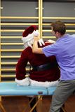 Male therapist massaging overworked Santa Claus. Male caucasian therapist massaging overworked Santa Claus Stock Photo