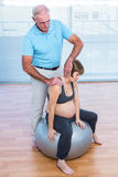 Male therapist massaging pregnant woman Stock Photos