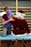 Male therapist massaging stressed Santa Claus. In fitness studio Stock Photos