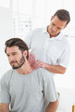 Male therapist massaging a young mans neck Stock Photos