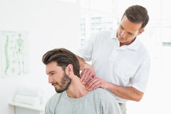 Male therapist massaging a young mans neck Royalty Free Stock Image