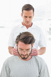 Male therapist massaging a young mans neck Royalty Free Stock Photography
