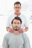 Male therapist massaging a young mans neck Stock Images