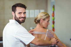 Male therapist measuring female patient back with goniometer. In clinic Royalty Free Stock Photos