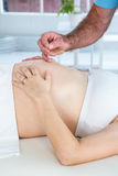 Male therapist performing reiki over belly of pregnant woman Stock Photo