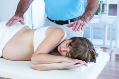 Male therapist performing reiki over pregnant woman. Male therapist performing reiki over pregnant women at health club Royalty Free Stock Images