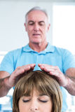 Male therapist performing reiki over woman. Male therapist performing reiki over women at health center Stock Images