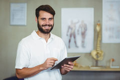 Male therapist using digital tablet in clinic. Portrait of male therapist using digital tablet in clinic Stock Images