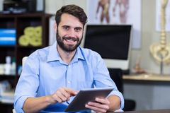 Male therapist using digital tablet in clinic. Portrait of male therapist using digital tablet in clinic Royalty Free Stock Photos