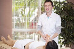 Male therapist at work. Male masseuse working with a female client at her home Stock Image