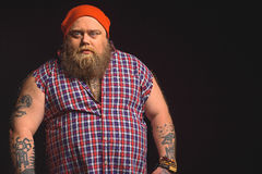 Male thick hipster expressing his seriousness. I am your nightmare. Serious fat man is looking at camera with threats. He is standing in stylish clothing Stock Photos
