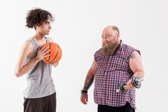 Male thick hipster showing his strength to thin guy. Look how I can. Confident fat bearded men is lifting dumbbell. Slim young boy is holding basketball ball and Royalty Free Stock Photography