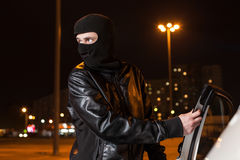 Male thief with balaclava on head opening car door. Male thief with balaclava on his head opening car door. Carjacking danger, car insurance marketing concept Royalty Free Stock Photos