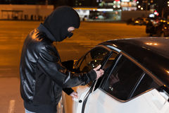 Male thief with balaclava on head opening car door. Male thief with balaclava on his head opening car door. Carjacking danger, car insurance marketing concept Stock Images