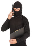 Male thief in balaclava, mobile phone, clipboard. Young male thief in balaclava with mobile phone and clipboard, white background Royalty Free Stock Photos