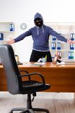 The male thief in balaclava in the office stock photography