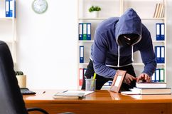 The male thief in balaclava in the office stock photos