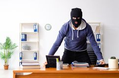 The male thief in balaclava in the office stock images
