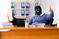 Male thief in balaclava in the office stock photos
