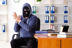 Male thief in balaclava in the office stock image