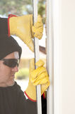 Thief breaking through window of home. Male thief with black hood, gloves and sunglasses trying to break in residential house, home, through window, with copy royalty free stock image