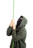 Male thief climbing on rope Royalty Free Stock Photos