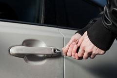 Male thief hands open car door with screwdriver. Male thief hands trying to open car door with screwdriver. Carjacker unlock vehicle. Carjacking danger Royalty Free Stock Image