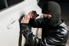 Male thief hands open car door with screwdriver. Male thief hands trying to open car door with screwdriver. Carjacker unlock vehicle. Carjacking danger Royalty Free Stock Photos