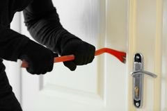 Male thief opening door. With scrap Royalty Free Stock Photos