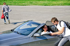 Male thief stealing handbag. From the car while his accomplice distracts female driver Stock Image