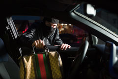 Male thief steals bag from car on parking. Male thief with balaclava on his head steals bag from car on parking. Carjacking danger concept. Carjacker unlock Stock Photos