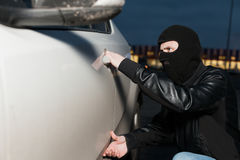 Male thief trying to open car door. Male thief with balaclava on his head trying to open car door. Carjacker unlock vehicle Royalty Free Stock Image