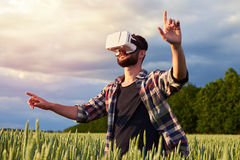 Male thinking in 3D glasses. Side view from below of man of middle age using 3D glasses surrounded by field of weed. Pointing with his fingers, mid shot Royalty Free Stock Images