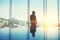 Male is thinking about future his company after unsuccessful meeting with investors. Silhouette of young asian manager is standing in conference room against big Stock Photo