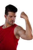 Male thlete flexing muscles. Male athlete flexing muscles while standing against white background Royalty Free Stock Photo