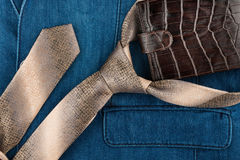 Male tie and wallet lying on denim suit. Royalty Free Stock Images