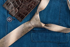 Male tie and wallet lying on denim suit. Royalty Free Stock Image