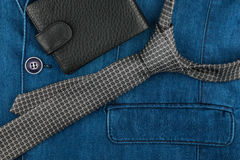 Male tie and wallet lying on denim suit. Stock Photo