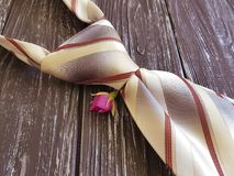 Male tie vintage on a wooden background, flower rose. Male tie on a wooden background flower rose vintage Royalty Free Stock Images