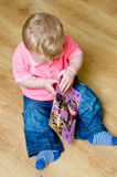 Male toddler with book. High angle view of male infant or toddler with book on wooden laminate floor Stock Images