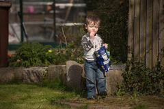 Male toddler eating crisps. Male toddler stood in garden eating packet of crisps royalty free stock images