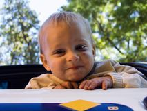 Male toddler playing outdoors. Portrait of happy male toddler playing outdoors with trees in background Royalty Free Stock Image