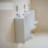 Male toilet. Row of three urinals in male toilet Royalty Free Stock Image
