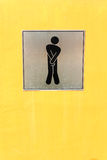 Male toilet sign. On yellow wall Stock Images