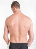 Male torso, back view. Rear view of a bare male torso wearing shorts Stock Photos