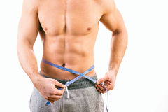Male torso and blue tape measure. On white background Royalty Free Stock Photo